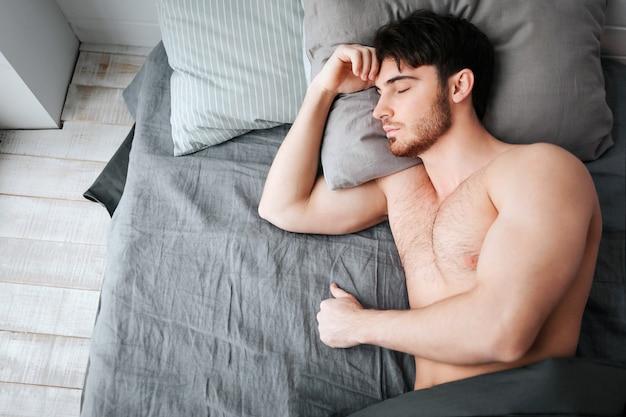 Seul jeune homme musclé, dormir dans son lit. il tient la tête sur l'oreiller. le jeune homme est nu. partie inférieure du corps recouverte d'une couverture grise.