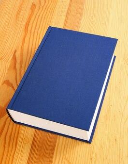 Seul livre bleu marine sur fond de bois