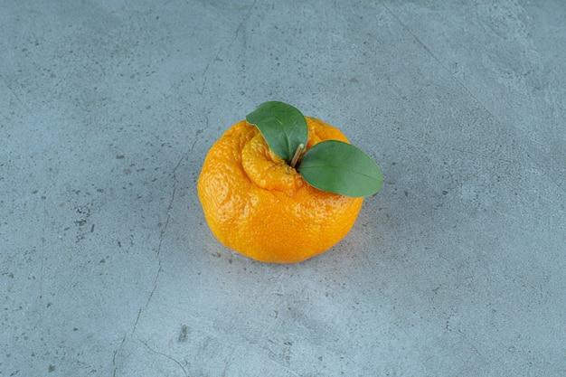 Un seul de mandarine mûre , sur le fond de marbre. photo de haute qualité