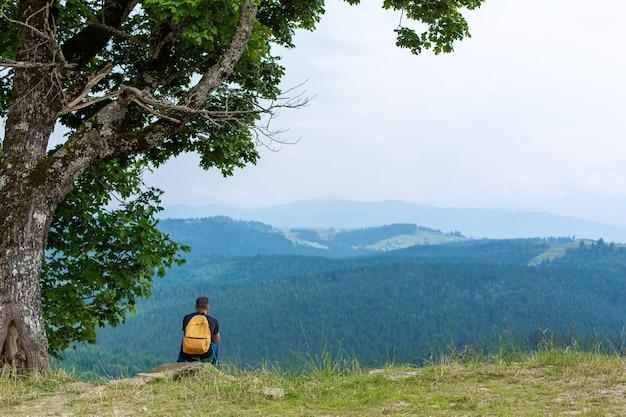 Seul mec assis sur la falaise et profiter du paysage paisible des montagnes vertes