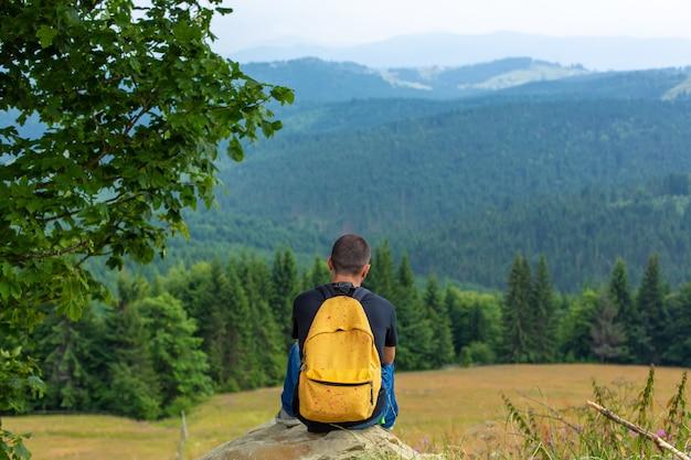 Seul mec assis sur la falaise et profitez d'un paysage paisible de montagnes verdoyantes. tranquillité d'esprit et détente.