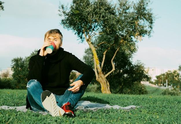 Seul, seul, seul homme d'âge moyen buvant du café dans le parc. concept de solitude, de distanciation sociale et d'auto-insaltion. concept de santé mentale, connexion à la nature