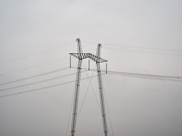 Seul support de pylône électrique dans un champ brumeux