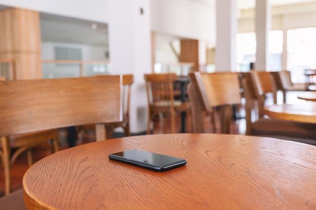 Un seul téléphone portable noir sur la table en bois
