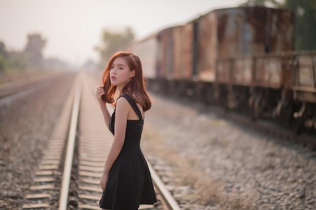 Seule jeune femme asiatique sur voie ferrée porte une robe noire sur train flou
