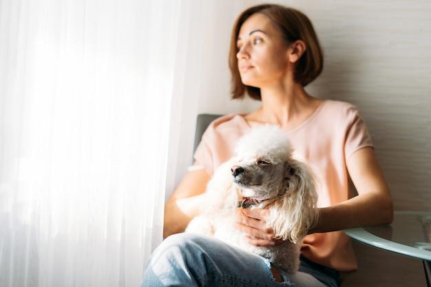 Seule jeune femme brune avec chien caniche sur les mains assis près de la fenêtre à la maison