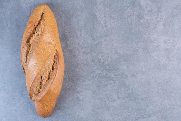 Seule miche de pain baton sur fond de marbre. photo de haute qualité