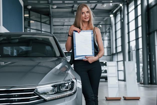 Une seule personne. fille et voiture moderne dans le salon. le jour à l'intérieur. acheter un véhicule neuf