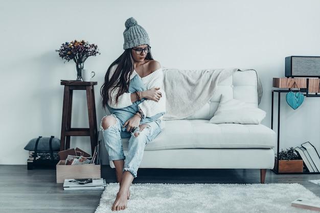 Seule avec ses pensées. belle jeune femme en tenue décontractée et bonnet en tricot embrassant l'oreiller