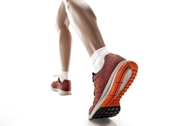La seule silhouette féminine caucasienne de coureur courant et sautant sur fond de studio blanc. le sprinter, le jogger, l'exercice, l'entraînement, le fitness, l'entraînement, le concept de jogging. vue arrière