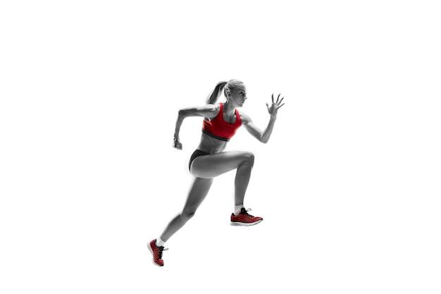 La seule silhouette féminine caucasienne de coureur courant et sautant sur fond de studio blanc. le sprinter, le jogger, l'exercice, l'entraînement, le fitness, l'entraînement, le concept de jogging.