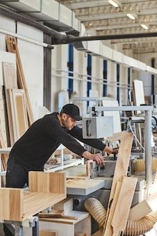 Seuls nos meilleurs feront le charpentier coupant du bois sur une scie électrique