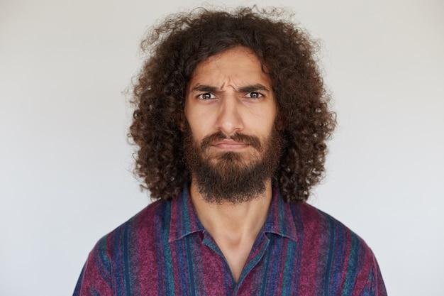 Sévère beau jeune homme bouclé brune avec barbe regardant sérieusement et fronçant les sourcils, vêtu d'une chemise décontractée à rayures