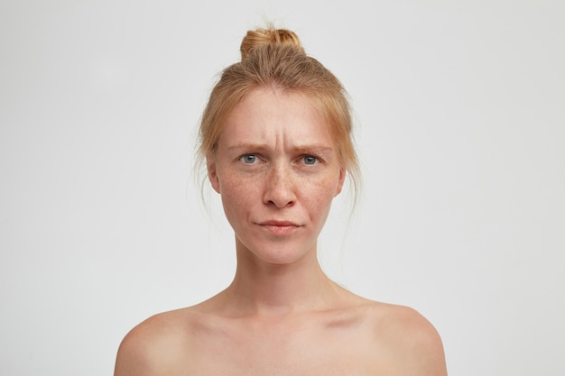 Sévère jeune femme rousse attrayante avec un maquillage naturel en pinçant les lèvres et en fronçant les sourcils tout en regardant sérieusement, isolé sur un mur blanc