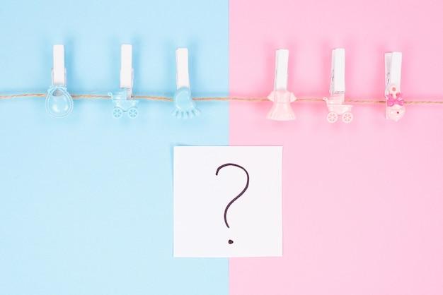 Le sexe révèle le concept d'invitation à une fête. la photographie d'arrière-plan de petites chevilles avec des jouets chariot isolé sur divisé en deux parties d'arrière-plan point d'interrogation au centre