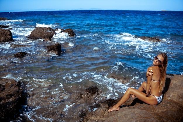 Sexuelle jeune fille dans l'océan posant