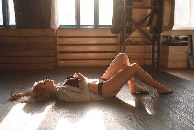 Sexy belle blonde posant en lingerie noire et une chemise blanche.