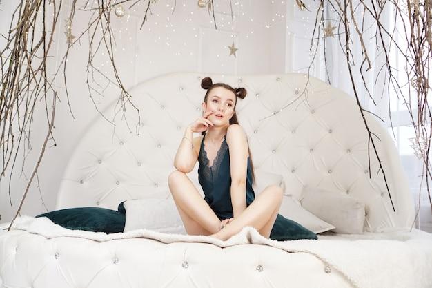 Sexy belle femme assise sur un grand lit blanc fille relaxante aux longs cheveux sains