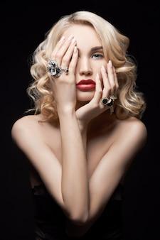 Sexy belle femme blonde aux cheveux longs. portrait de femme parfaite sur mur noir. des cheveux magnifiques et de beaux yeux. beauté naturelle, peau propre, soins du visage et cheveux. cheveux forts et épais. bijoux