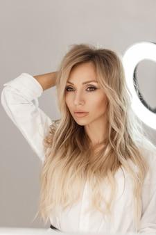 Sexy belle femme avec une coiffure blonde en chemise blanche