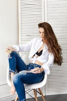 Sexy belle fille en jeans chemise blanche sur chaise