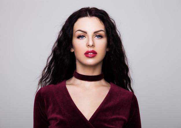 Sexy belle mannequin portant une robe de luxe en velours avec des cheveux bouclés et des lèvres rouges sur gris