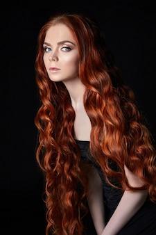 Sexy belle rousse aux cheveux longs. portrait de femme parfaite sur fond noir. cheveux magnifiques et yeux profonds. beauté naturelle, peau propre, soins du visage et cheveux. cheveux forts et épais