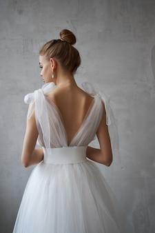 Sexy fashion belle femme en robe est debout contre le mur. maquillage parfait, portrait romantique d'une femme blonde