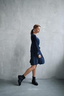 Sexy fashion belle femme en robe est debout contre le mur