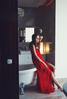 Sexy femme aux cheveux bouclés dans une robe rouge