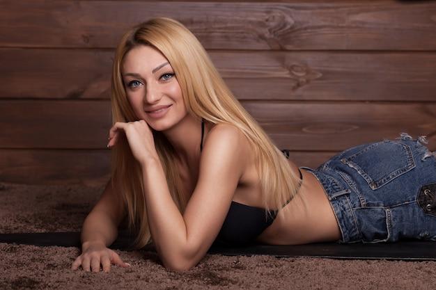 Sexy femme blonde portant un short en jean et couché