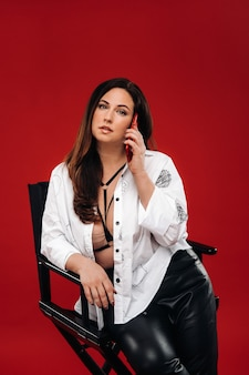Sexy femme brûlante dans une chemise blanche assise sur une chaise avec un téléphone rouge sur un mur rouge