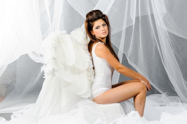 Sexy femme brune dans un costume d'ange montre ses jambes sexy et s'assoit sur un nuage.