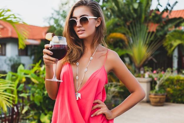 Sexy femme élégante en tenue de fête de mode en vacances d'été avec un verre de cocktail s'amuser sur la piscine