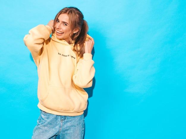 Sexy femme insouciante posant près du mur bleu. modèle positif s'amusant