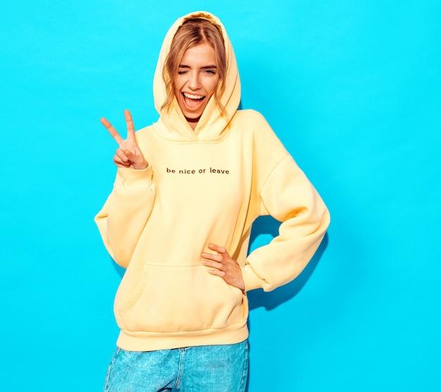 Sexy femme insouciante posant près du mur bleu. modèle positif s'amuser clins d'oeil et montre le signe de la paix