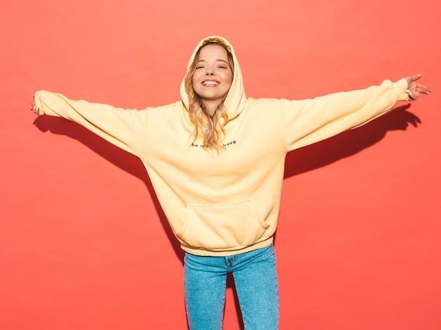 Sexy femme insouciante posant près du mur rose. modèle positif s'amusant, levant les mains