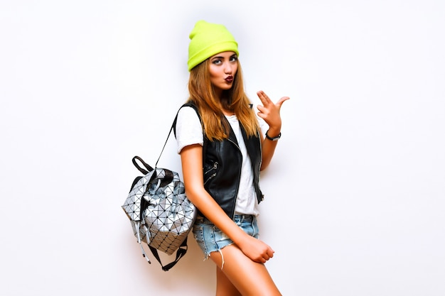 Sexy femme de mode superbe posant près du mur blanc, look hipster de style rue, gilet en cuir de motard, mini shorts de vue, chapeau néon et sac à dos, corps sexy git bronzé, yo, butin, été, flash, drôle, fou