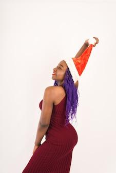Sexy femme noire de nouvel an avec une robe rouge, maquillage lumineux avec bonnet de noel rouge