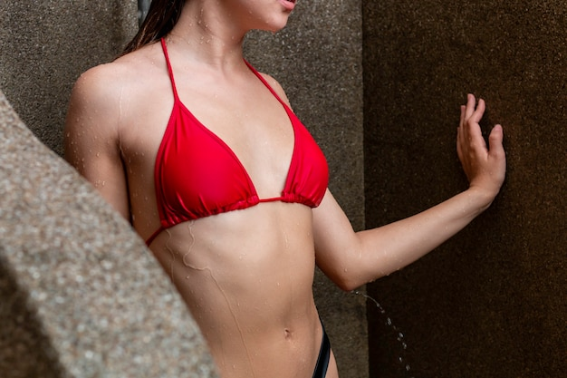 Sexy femme de race blanche en bikini rouge sous la douche à l'extérieur.