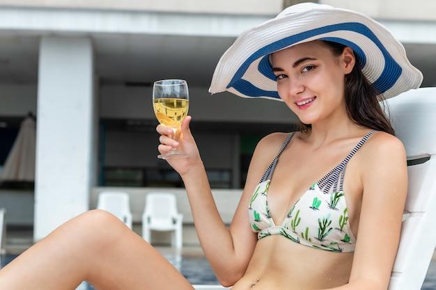 Sexy femme de race blanche portant un bikini assis sur la plage de chaise et boire un cocktail près de la piscine.