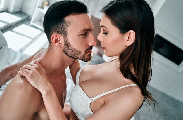 Le sexy et la femme en sous-vêtements assis sur le lit