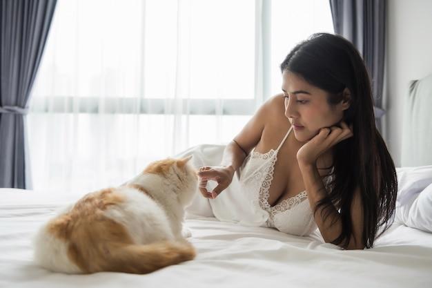 Sexy femme tan asiatique en pyjama jouant avec chat exotique shorthair brun
