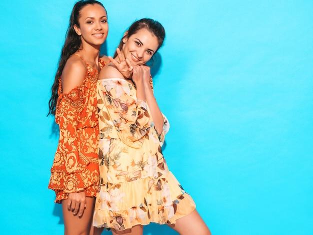 Sexy femmes insouciantes posant près du mur bleu. amusant et étreignant. les modèles montrent une bonne relation. femme sans maquillage