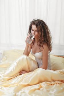 Sexy fille caucasienne mince bouclés assis dans un lit du matin tenir un verre d'eau
