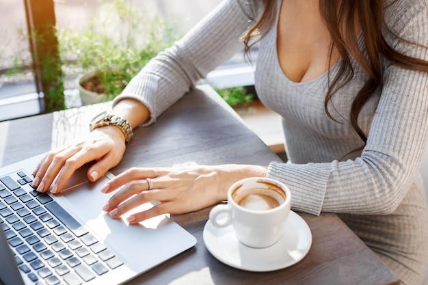 Sexy fille travaillant sur un ordinateur portable au café