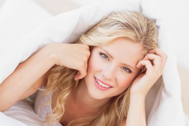 Sexy jeune blonde souriante à la caméra de sous la feuille