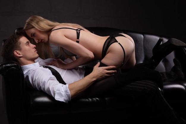 Sexy jeune couple amoureux s'embrassant passionnément allongé sur un canapé noir.