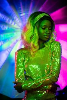 Sexy jeune femme au néon. fille élégante en robe étincelante posant sur un fond coloré ou multicolore lumineux dans un style disco. concept vogue
