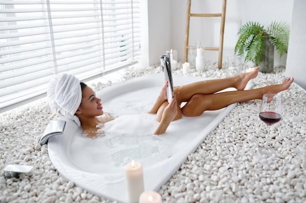 Sexy jeune femme lit un magazine dans un bain moussant. personne de sexe féminin dans la baignoire, soins de beauté et de santé au spa, traitement de bien-être dans la salle de bain, cailloux et bougies sur fond